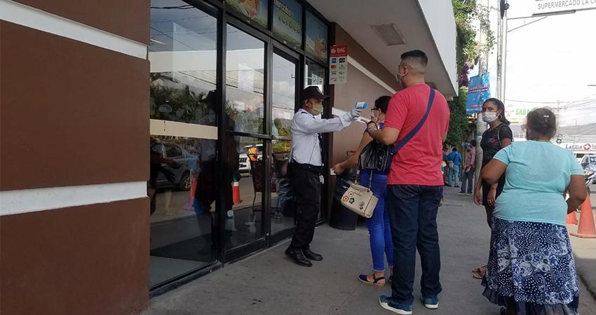 Los guardas de seguridad han sido capacitados para tomar la temperatura a los clientes. Foto: Roberto Mora/Radio ABC Stereo